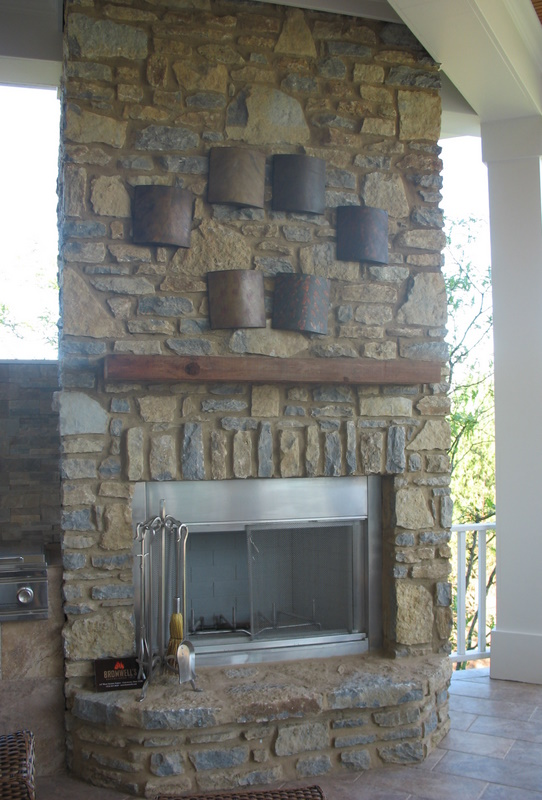 The covered porch off the kitchen features a stone fireplace and built-in grill.