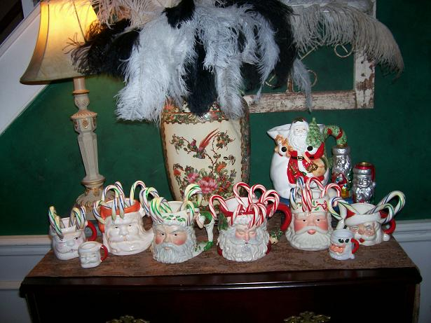 A group of Santa mugs with candy canes in them