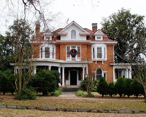 A large brick house with wreath over front door