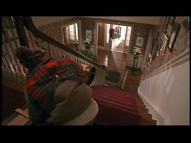Kevin decides to take a sled ride down the stairs.