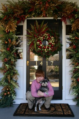 front porch with wreath and boy holding dog