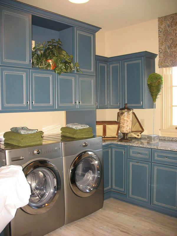 The laundry room with blue cabinets.