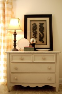 dresser with lamp and artwork
