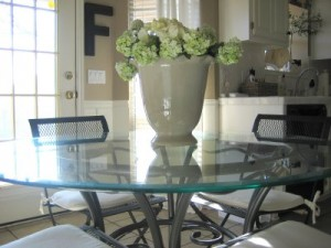 A glass dining room table with vase