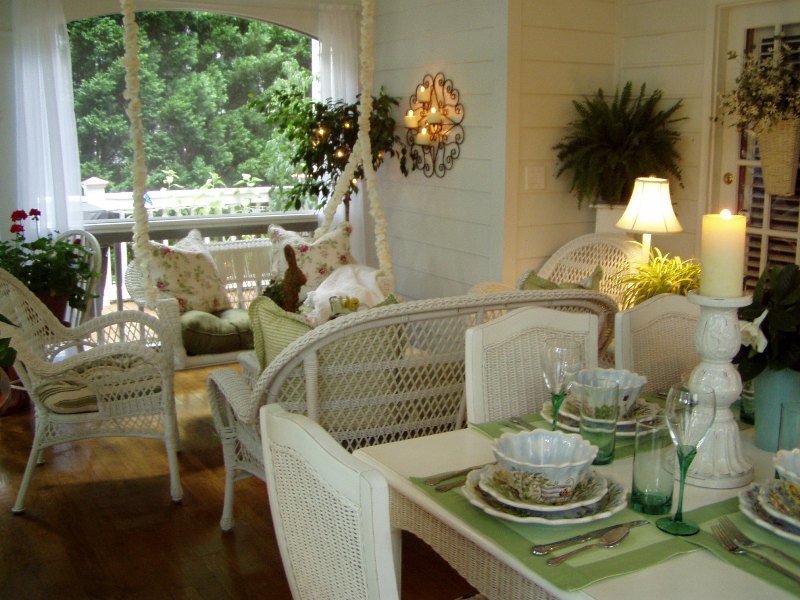 screened porch with porch swing and dining table with wicker chairs