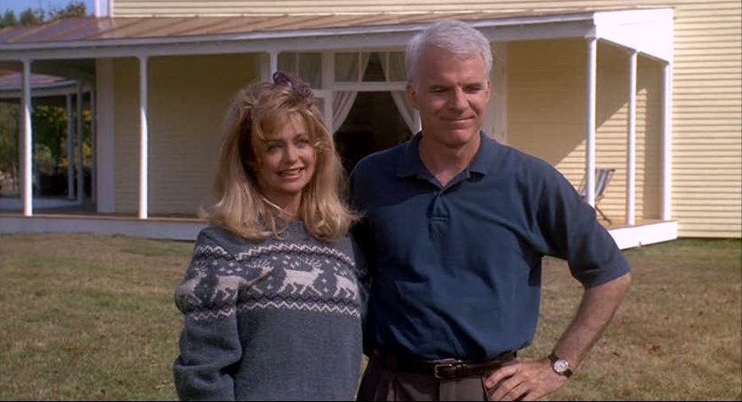 Gwen and Davis standing together in front of their house in Housesitter movie