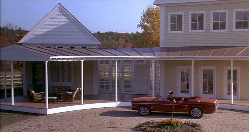 A red convertible car parked in front of the yellow house