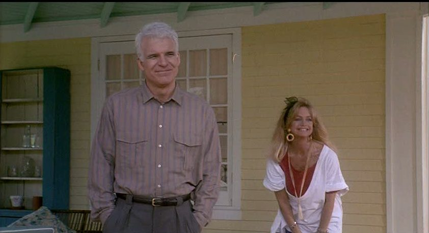 Steve Martin and Goldie Hawn standing on front porch of yellow house