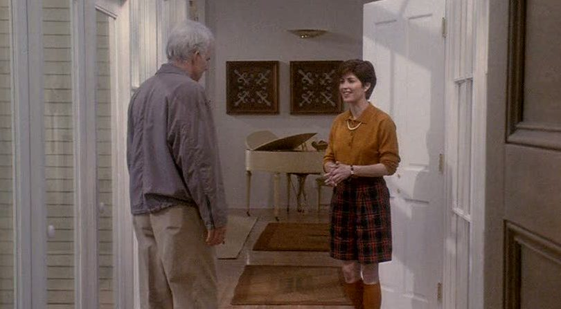 Steve Martin and Dana Delaney talking in front of piano