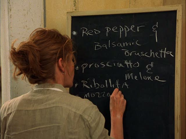 A person standing in front of a blackboard, with Diane Lane