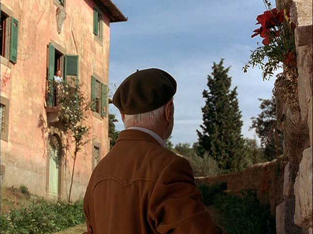An old man standing in front of the villa