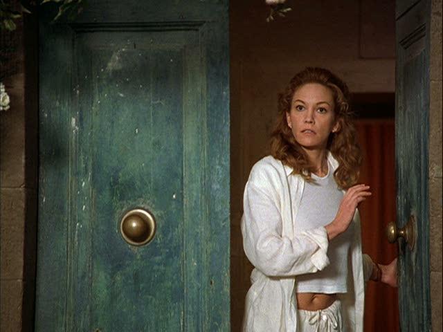 Diane Lane standing in front of a door