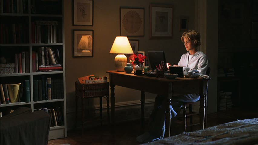 Meg Ryan works on her laptop in her apartment