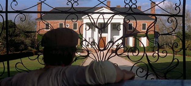 Ryan Gosling looking through iron gates at Boone Hall Plantation house