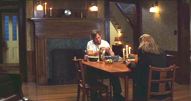 Noah and Allie sitting at the table in the dining room in front of the fireplace