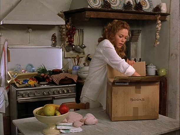 Diane Lane in the villa kitchen opening a box