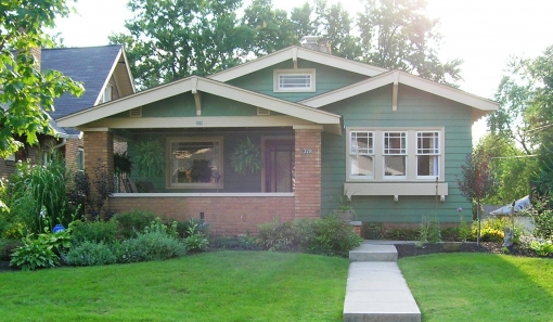 green bungalow with red brick porch