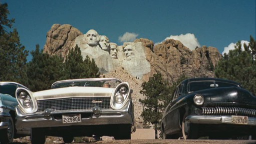 cars parked in lot below Mount Rushmore