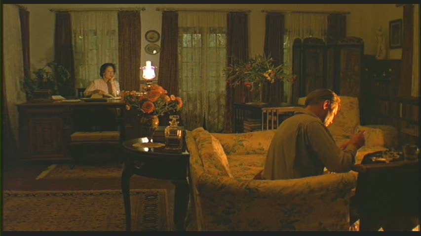 A man and a woman sitting in the living room at night