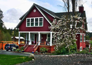 exterior view of red cottage with white trim and front porch on Bainbridge Island