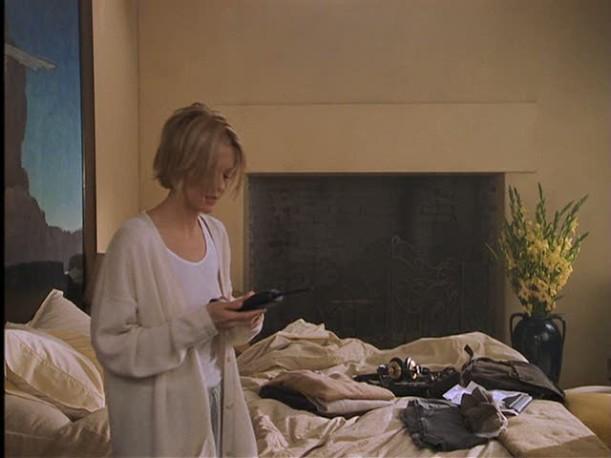 Meg Ryan walks past bed