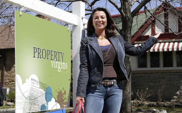 Sandra Rinomato standing in front of a Property Virgins sign