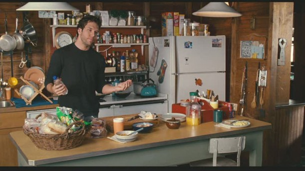 Dane Cook standing at kitchen island in cabin
