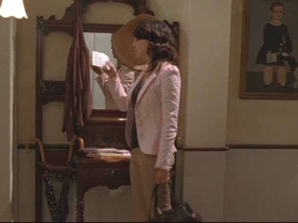 Lorelai standing in entry hall reading a note