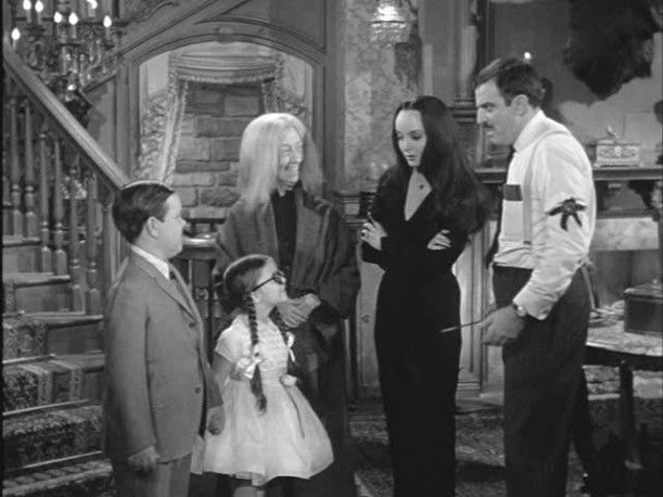 the Addams family gathered at base of staircase