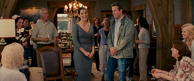 Sandra Bullock and Ryan Reynolds standing in front of dining table