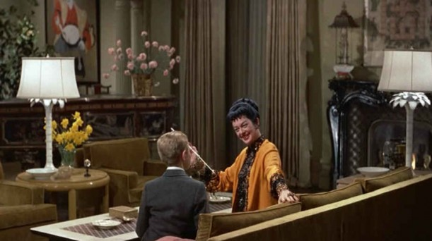 Auntie Mame talking to her nephew on the sofa