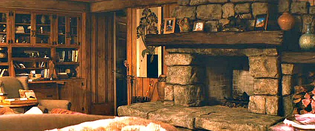large stone fireplace with rustic wood mantel in bedroom