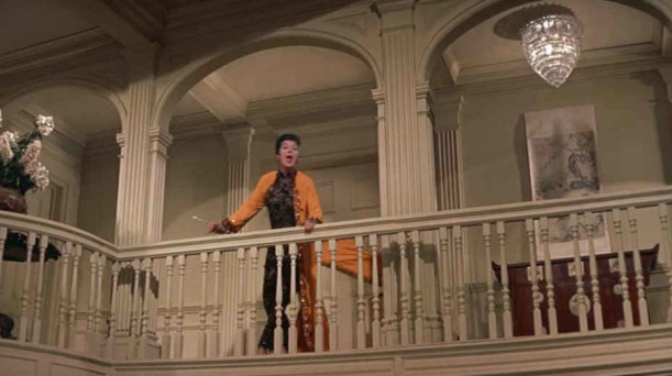 Auntie Mame standing at second story railing above party