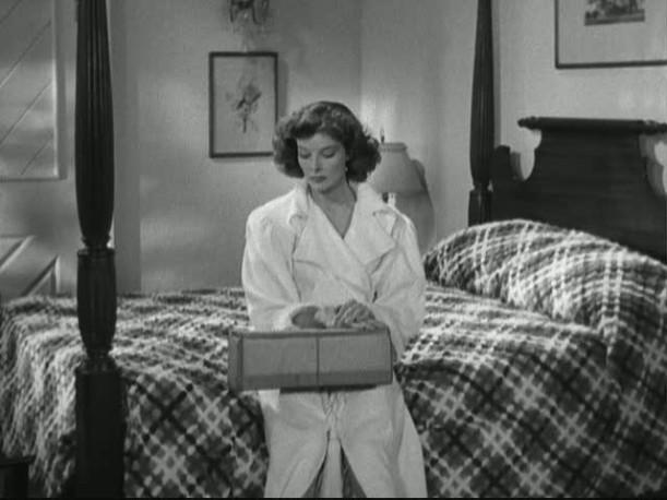 Katharine Hepburn sitting on a bed