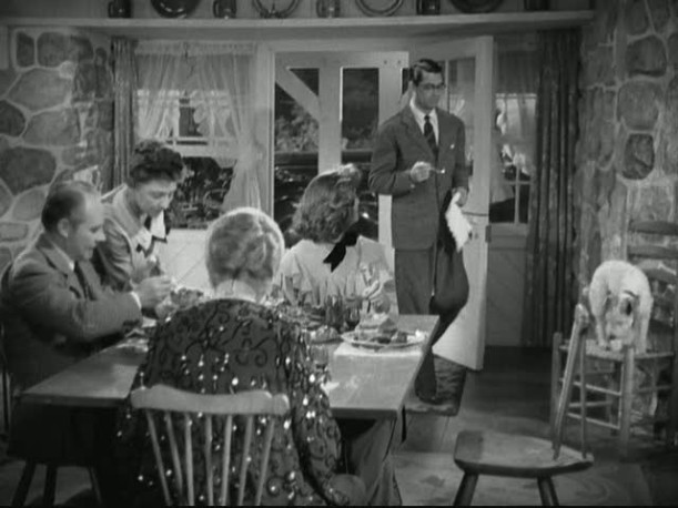 Cary Grant standing beside dining table
