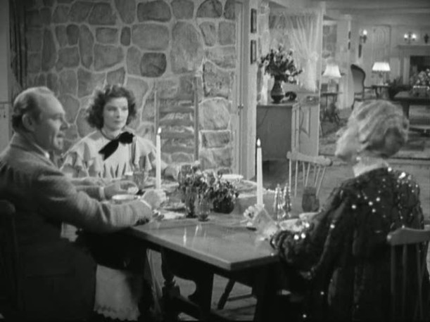 Katharine Hepburn at head of dining table with stone wall