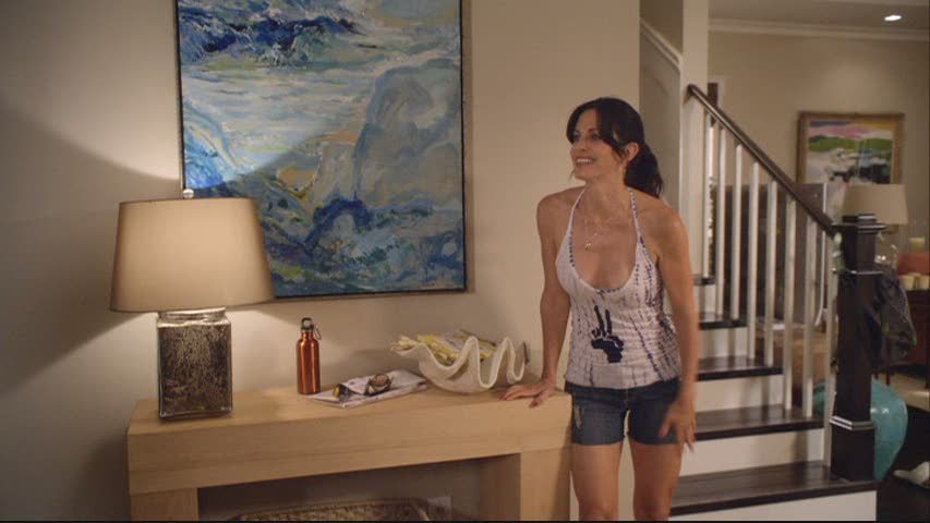 Courteney Cox in entry way with blue painting
