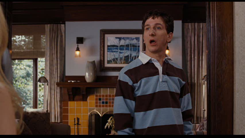 Paul Rust standing in front of fireplace