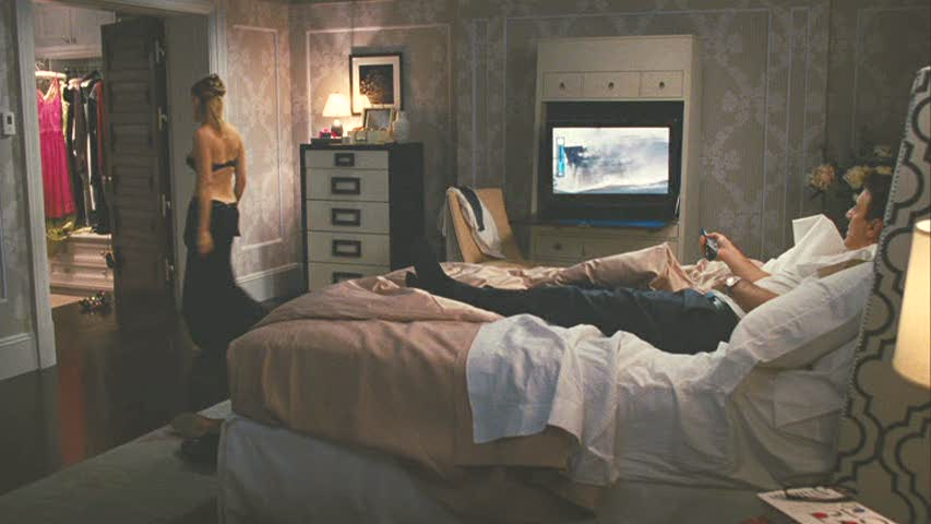 A person sitting on a bed in a room