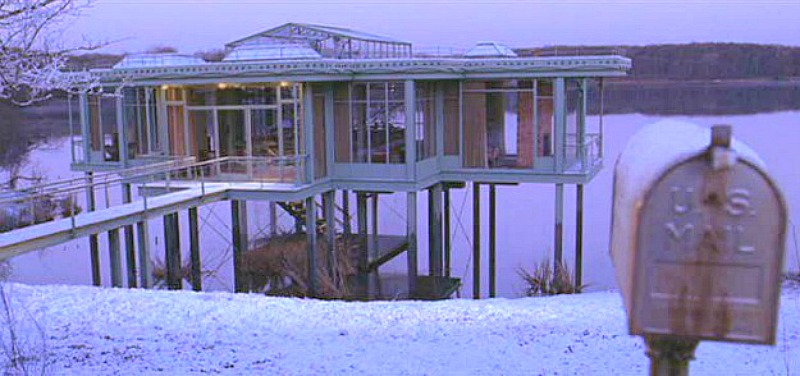 the glass lake house covered in snow