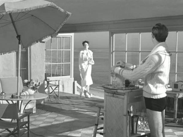 Mildred Pierce standing in open doorway with beach behind her