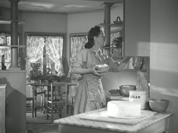 Joan Crawford cooking in Mildred Pierce\'s kitchen