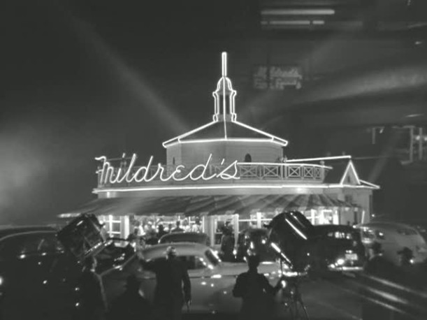 Mildred\'s restaurant with neon sign and vintage cars parked outside