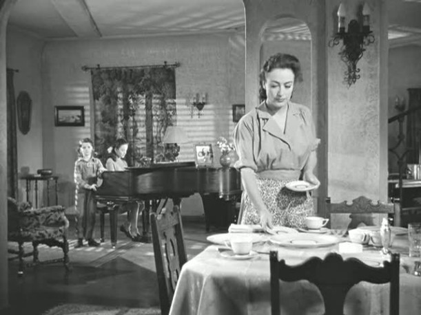 Joan Crawford standing at dining room table with piano in background