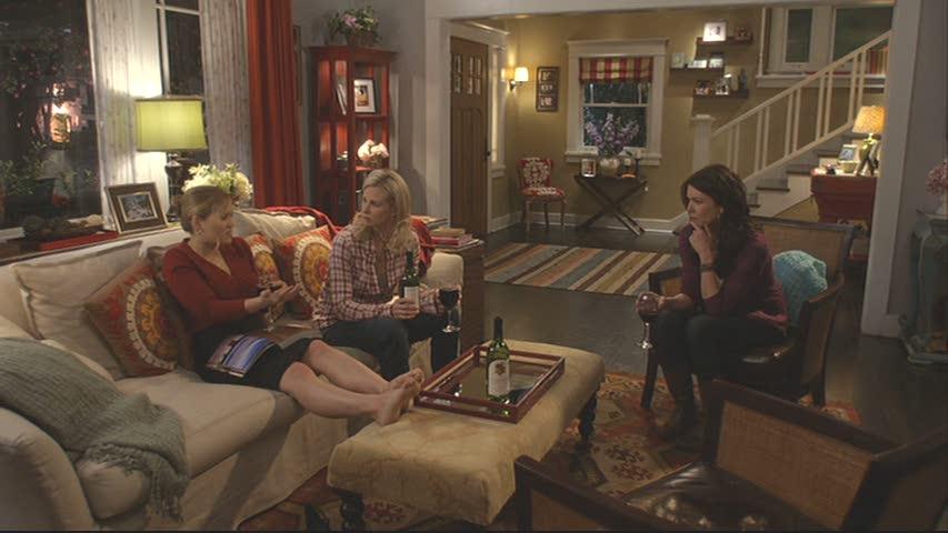 cast members sitting in living room