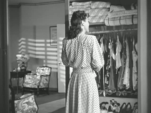 Joan Crawford looking into a closet filled with women\'s swimsuits