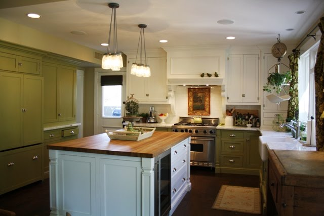 A kitchen with green lower cabinets and white uppers