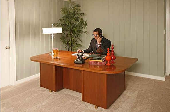 man dressed like Don Draper sitting at desk talking on phone
