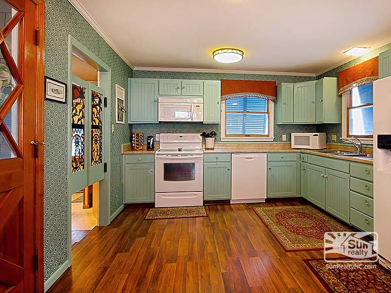 A kitchen with a wooden floor and painted cabinets after remodel