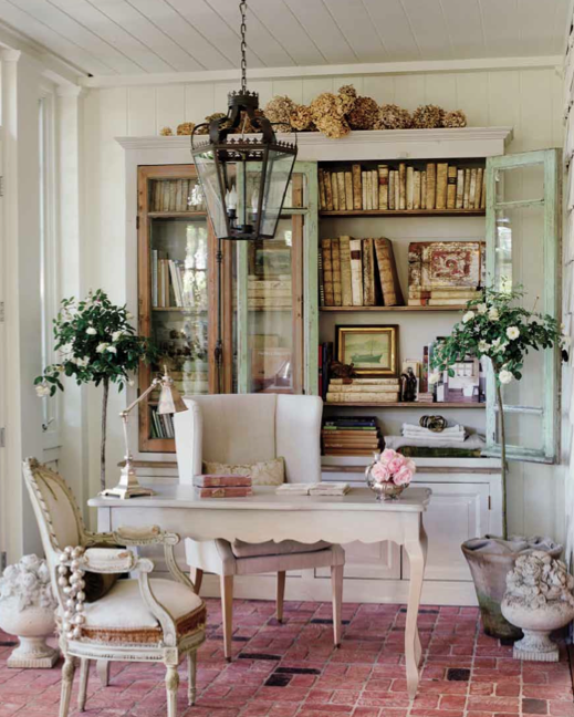 desk and hutch in sunroom with brick floor